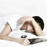 El adolescente duerme con la tableta Fotos de archivo