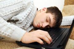 El adolescente duerme en el ordenador portátil Fotografía de archivo libre de regalías