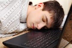 El adolescente duerme en el ordenador portátil Imágenes de archivo libres de regalías
