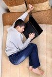 El adolescente duerme en el ordenador portátil Fotografía de archivo