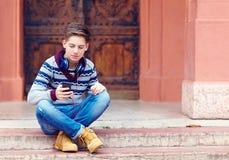 El adolescente elegante escucha la música en el teléfono elegante Fotografía de archivo