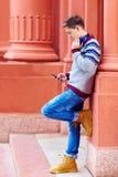 El adolescente elegante escucha la música en el teléfono elegante Imagen de archivo libre de regalías