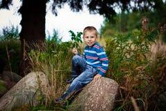 El adolescente elegante se sienta en roca Fotografía de archivo libre de regalías