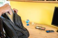 El adolescente embala una mochila a la escuela antes de salir de la casa Fotos de archivo