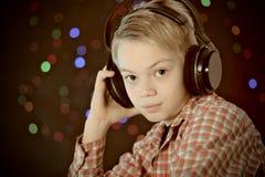 El adolescente en auriculares escucha la música Imagen de archivo