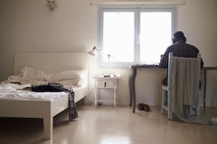 El adolescente en auriculares trabaja en el escritorio en el dormitorio, visión trasera Imagen de archivo