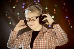 El adolescente en auriculares y con la guitarra escucha la música Imagen de archivo libre de regalías