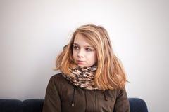El adolescente en caliente outwear sentarse en el sofá azul Imagen de archivo libre de regalías