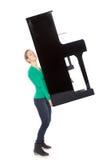 El adolescente en camisa verde lleva el piano Fotos de archivo libres de regalías
