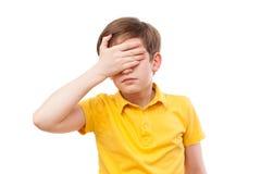 El adolescente en camiseta amarilla cierra sus ojos a mano Foto de archivo