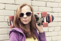El adolescente en gafas de sol sostiene el monopatín Imagenes de archivo