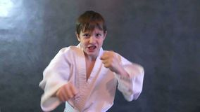 El adolescente en karate de la lucha del kimono da a puños que agitan la cámara lenta metrajes