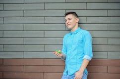 El adolescente en la camisa azul y los tejanos dan sostener el artilugio Imágenes de archivo libres de regalías