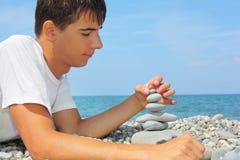 El adolescente en la costa, crea la pirámide del guijarro Imagen de archivo