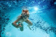 El adolescente en la máscara y el tubo respirador nadan bajo el agua. Imágenes de archivo libres de regalías