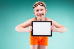 El adolescente en pantalones cortos anaranjados y los vidrios que nadan sostienen la tableta vacía Imágenes de archivo libres de regalías