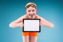El adolescente en pantalones cortos anaranjados y los vidrios que nadan sostienen la tableta vacía Fotografía de archivo