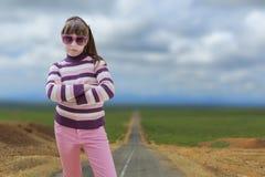El adolescente en rosa lleva las gafas de sol con el camino en fondo Foto de archivo