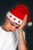El adolescente en Santa Hat siente dolor de cabeza Foto de archivo