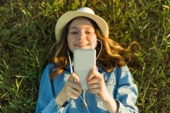 El adolescente en sombrero con los auriculares miente en la hierba verde y mira en el teléfono Foco en el smartphone, visión supe Imágenes de archivo libres de regalías
