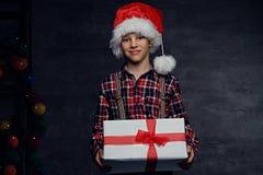 El adolescente en sombrero del ` s de Papá Noel sostiene la caja de regalo Fotos de archivo