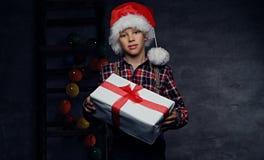 El adolescente en sombrero del ` s de Papá Noel sostiene la caja de regalo Foto de archivo