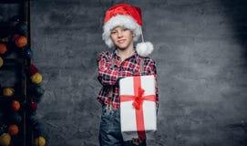 El adolescente en sombrero del ` s de Papá Noel sostiene la caja de regalo Imagenes de archivo
