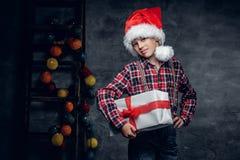 El adolescente en sombrero del ` s de Papá Noel sostiene la caja de regalo Imagen de archivo