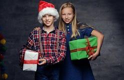 El adolescente en sombrero del ` s de Papá Noel y muchacha rubia sostiene las cajas de regalo Imágenes de archivo libres de regalías