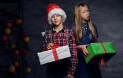 El adolescente en sombrero del ` s de Papá Noel y muchacha rubia sostiene las cajas de regalo Foto de archivo libre de regalías