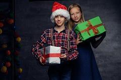 El adolescente en sombrero del ` s de Papá Noel y muchacha rubia sostiene las cajas de regalo Fotos de archivo libres de regalías