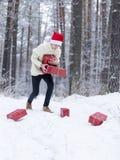 El adolescente en el sombrero Santa Claus recoge los regalos en un bosque nevoso adentro Imagen de archivo