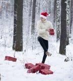 El adolescente en el sombrero Santa Claus recoge los regalos en un bosque nevoso adentro Fotografía de archivo libre de regalías