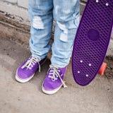 El adolescente en tejanos se coloca con el monopatín Foto de archivo libre de regalías