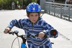 El adolescente en un casco y con la bicicleta Foto de archivo