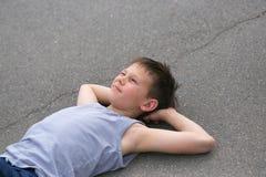 El adolescente en un chaleco descansa sobre la reclinación del asfalto Imagenes de archivo