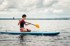 El adolescente en un traje mojado flota sentando un supsurf en el lago Imagenes de archivo