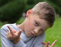 El adolescente en una actitud se sienta en un césped verde Foto de archivo libre de regalías
