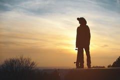 El adolescente en una camiseta y un casquillo que se oponen con un tablero en la ciudad al contexto de la puesta del sol urbana Fotografía de archivo libre de regalías
