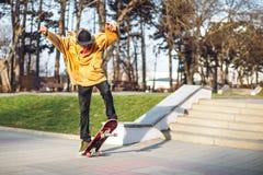El adolescente en una camiseta y un casquillo salta con un tablero en la ciudad contra el contexto de la luz urbana de la puesta  Fotos de archivo libres de regalías