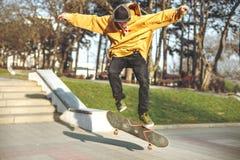 El adolescente en una camiseta y un casquillo salta con un tablero en la ciudad contra el contexto de la luz urbana de la puesta  Fotografía de archivo libre de regalías