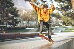 El adolescente en una camiseta y un casquillo salta con un tablero en la ciudad contra el contexto de la luz urbana de la puesta  Fotos de archivo
