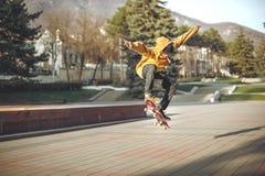 El adolescente en una camiseta y un casquillo salta con un tablero en la ciudad contra el contexto de la luz urbana de la puesta  Foto de archivo libre de regalías