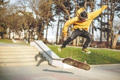 El adolescente en una camiseta y un casquillo salta con un tablero en la ciudad contra el contexto de la luz urbana de la puesta  Imágenes de archivo libres de regalías