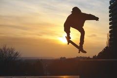 El adolescente en una camiseta y un casquillo salta con un tablero en la ciudad contra el contexto de la puesta del sol urbana Fotos de archivo libres de regalías