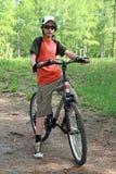 El adolescente en una madera en una bicicleta Foto de archivo
