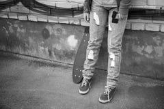 El adolescente en vaqueros se coloca con el monopatín Fotografía de archivo libre de regalías