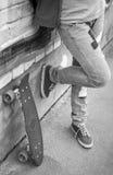 El adolescente en vaqueros se coloca con el monopatín Foto de archivo