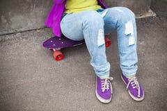 El adolescente en vaqueros y gumshoes se sienta en el monopatín Imagen de archivo