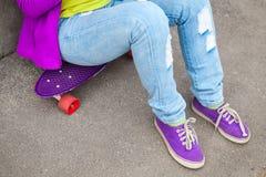 El adolescente en vaqueros y gumshoes se sienta en un monopatín Imagen de archivo